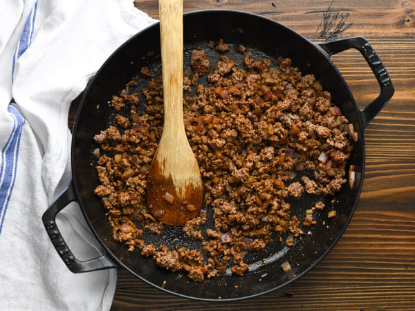 Process shot showing how to make cheesy taco skillet with ground beef and rice