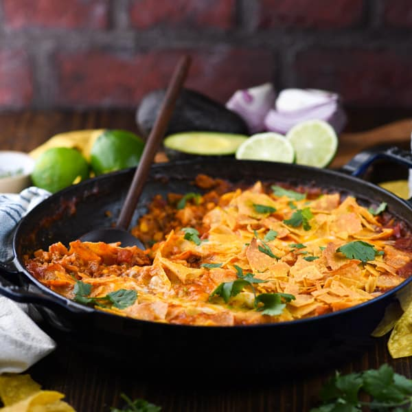 Square front shot of a cheesy taco skillet with rice in front of a brick wall