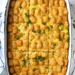 Overhead image of tater tot breakfast casserole with sausage in a white baking dish on a white table