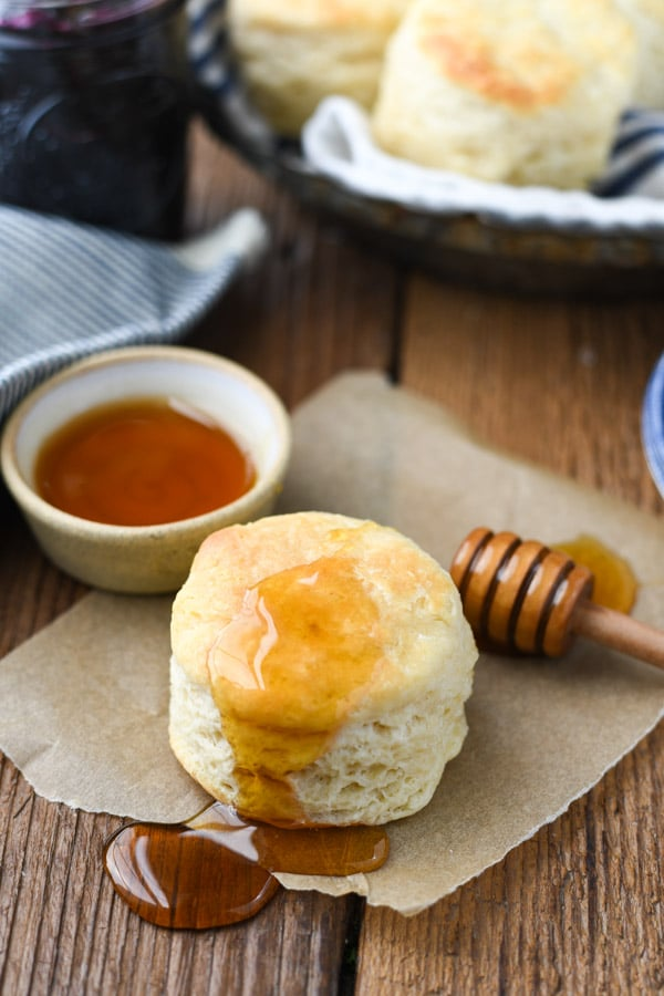 Homemade buttermilk biscuits on a wooden table with honey