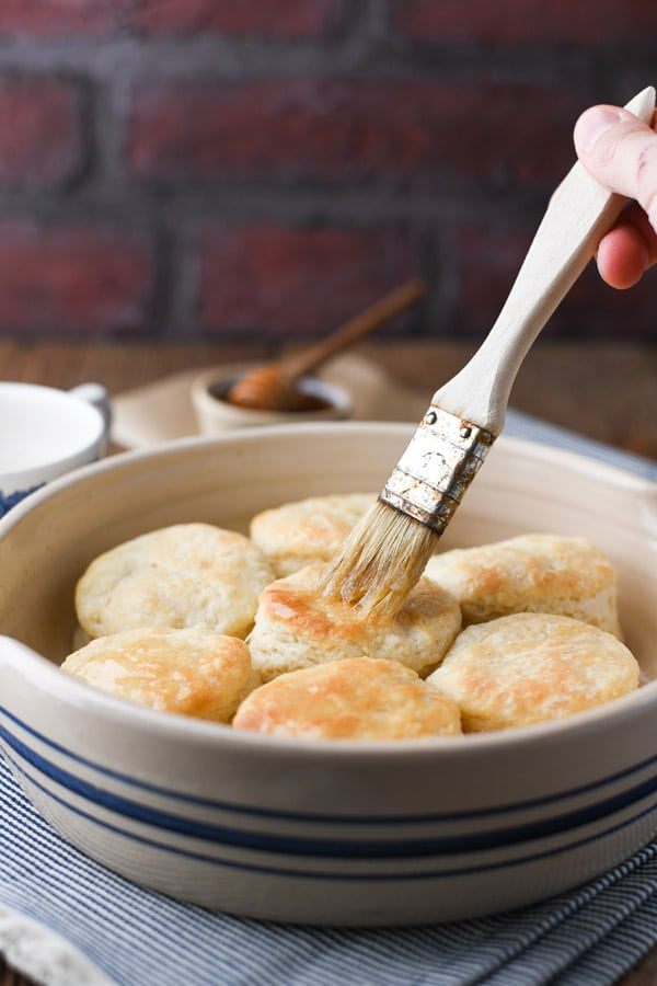 Brushing butter on a pan of buttermilk biscuits
