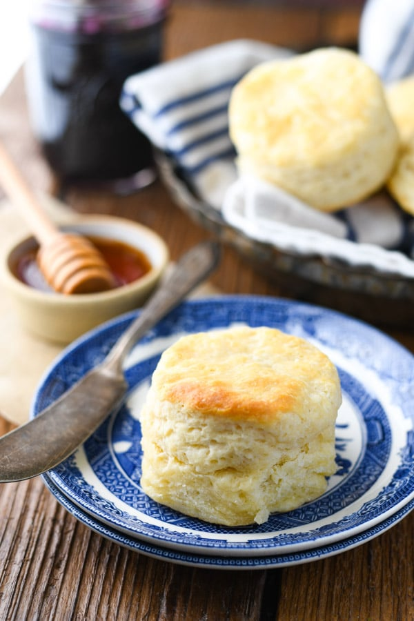 Side shot of tall and flaky buttermilk biscuits on a blue and white plate