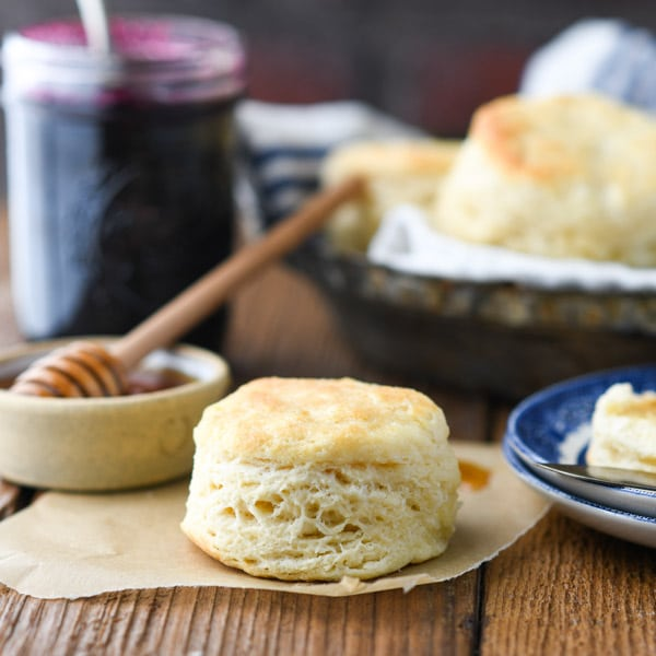 Simple 3 ingredient biscuit recipe on a wooden table with honey and jam in the background