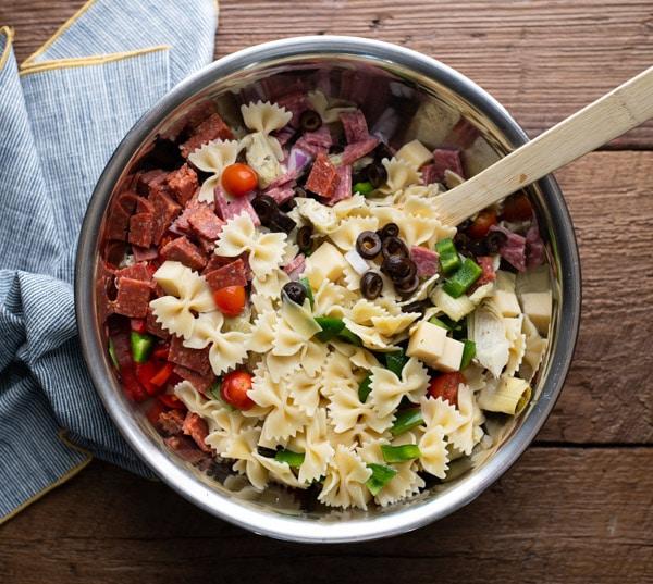 Process shot showing how to make antipasto pasta salad