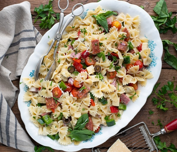 Square overhead shot of bow tie antipasto pasta salad on a white serving platter