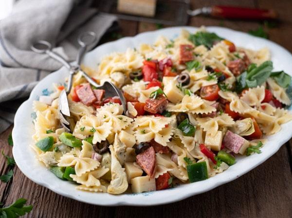 Horizontal shot of a serving bowl full of cold antipasto pasta salad