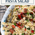 Close up shot of a platter of antipasto pasta salad recipe with text title box at top