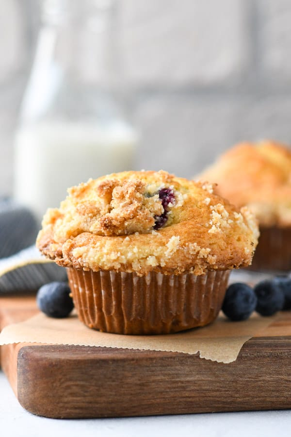 Close up side shot of blueberry muffins with crumb topping on a wooden cutting board