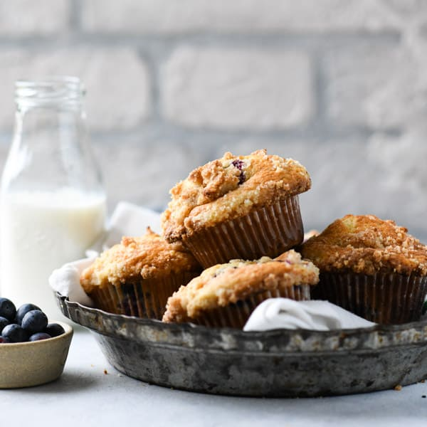 Square image of a basket of bake shop blueberry muffins on a white table