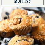 Close up shot of blueberry muffins with crumb topping and a text title box at top
