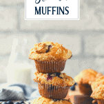 Stack of three blueberry streusel muffins with text title overlay