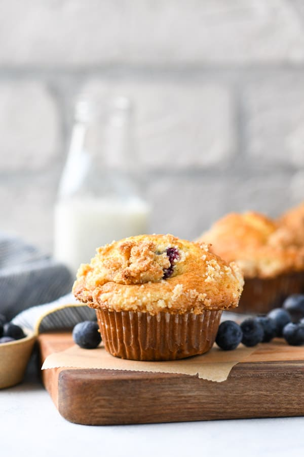Side shot of blueberry muffins with streusel topping on a wooden cutting board