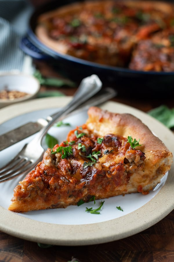 Slice of cast iron skillet deep dish pizza on a white plate