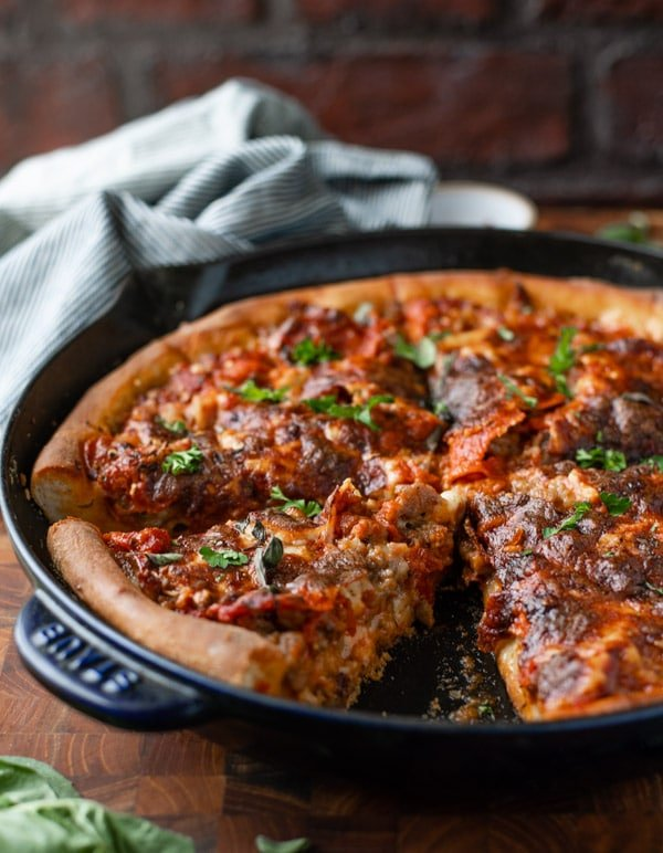 Side shot of cast iron skillet deep dish pizza on a table in front of a brick wall