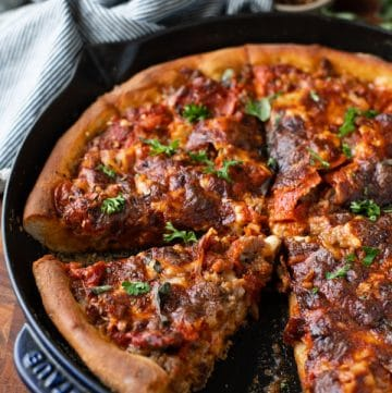 Close up side shot of a cast iron skillet pizza on a wooden board