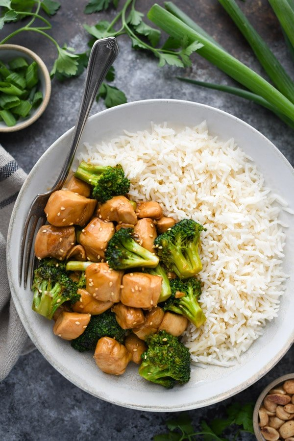 Overhead shot of a bowl of easy chicken and broccoli stir fry and a side of rice.