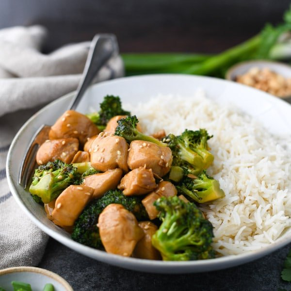 Square side shot of a bowl of easy chicken and broccoli stir fry recipe served with rice