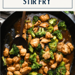 Pan of chicken stir fry with broccoli and text title box at top