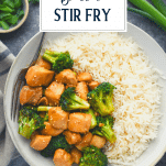 Overhead shot of a bowl of chinese chicken and broccoli stir fry with a side of rice and text title overlay