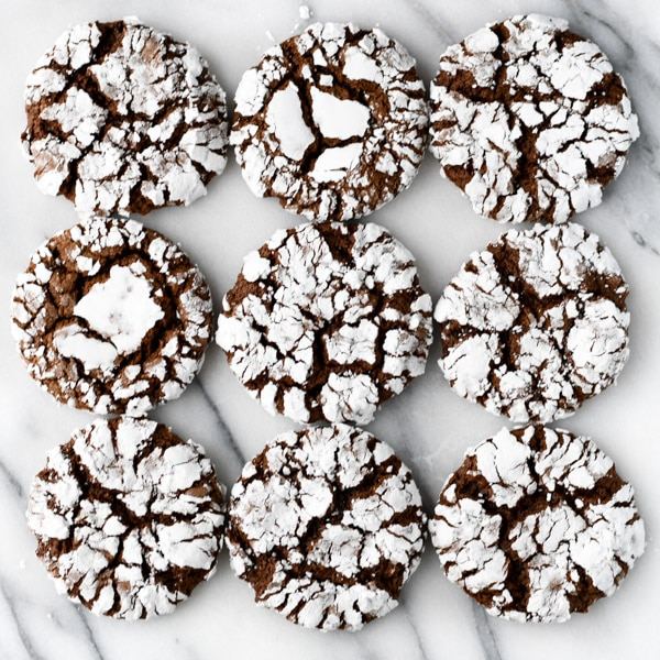 Close overhead shot of chocolate crinkle cookies with cake mix on a white surface