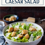 Side shot of a bowl of caesar salad on a wooden table with text title box at top