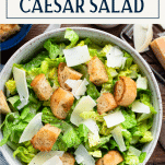 Overhead image of a bowl of homemade caesar salad with text title box at top