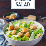 Side shot of a bowl of classic caesar salad with text title overlay