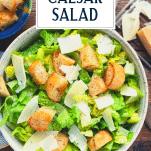 Overhead shot of caesar salad in a bowl with text title overlay