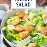 Close up side shot of a bowl of classic caesar salad with text title overlay