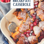 Overhead image of a sweet croissant breakfast casserole with berries and a text title box at top