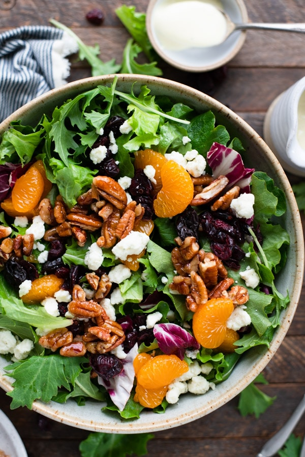 Overhead image of a bowl of salad with mandarin oranges and homemade dressing