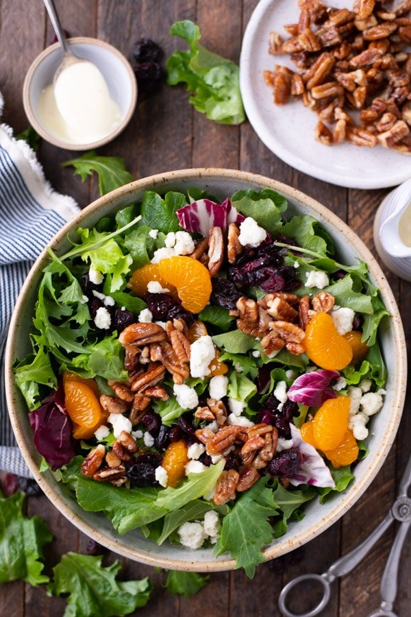 Overhead shot of a bowl of house salad with mandarin oranges on a wooden table