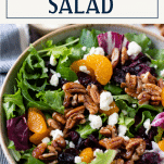 Close up shot of a bowl of salad with mandarin oranges and text title box at top