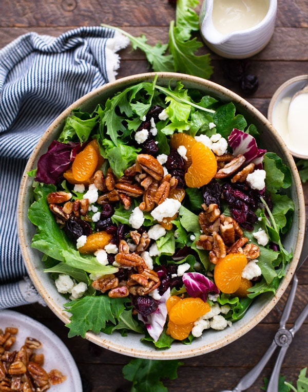 Overhead shot of house salad recipe with creamy salad dressing on a wooden table