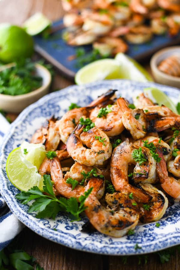 Close up side shot of the best grilled shrimp recipe garnished with parsley and limes on a blue and white plate