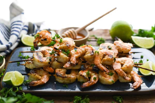 Horizontal shot of a platter of grilled shrimp skewers