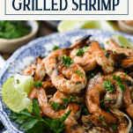 Close up side shot of grilled shrimp recipe on a plate with text title box