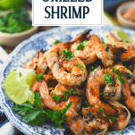 Side shot of a plate of grilled shrimp with text title overlay