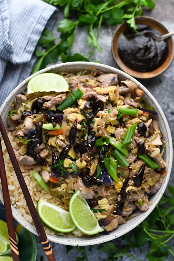Overhead shot of a bowl of moo shu pork with a side of hoisin sauce and rice