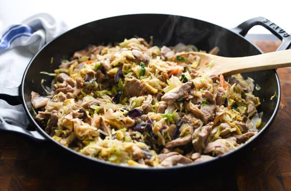 Horizontal shot of authentic moo shu pork recipe in a cast iron skillet