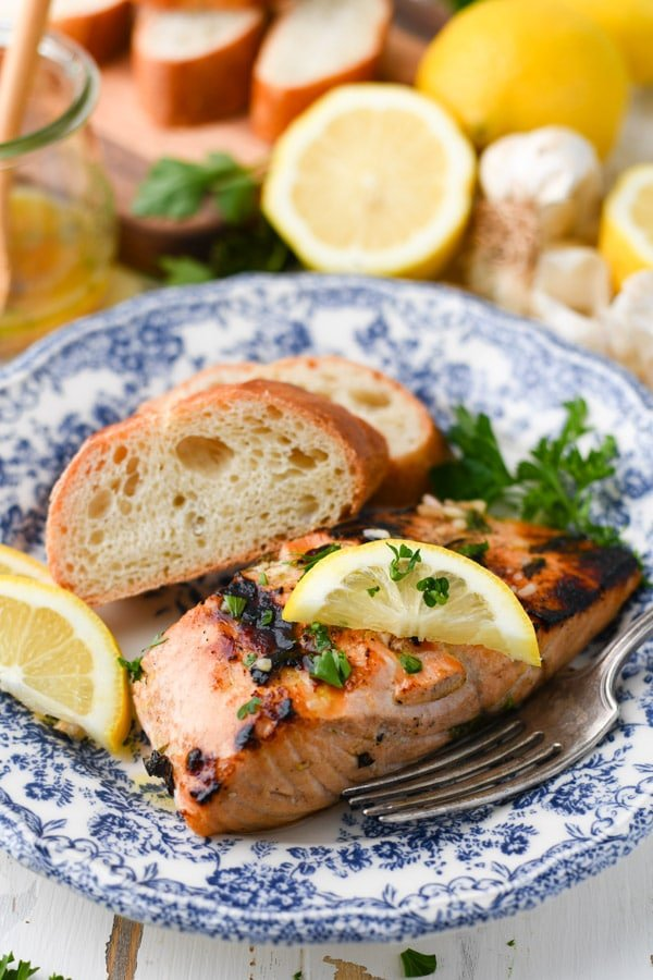 Close up side shot of a piece of marinated grilled salmon on a blue and white plate with fresh herbs and lemon