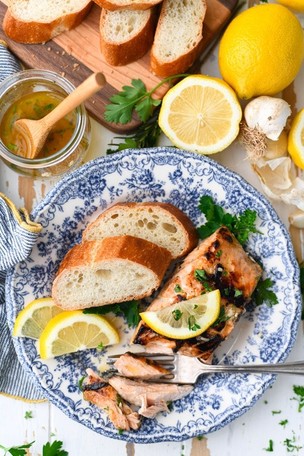 Overhead shot of grilled salmon marinade on a blue and white plate with fresh lemon