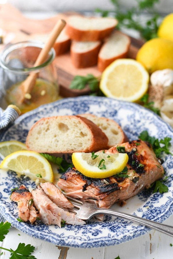 Side shot of grilled salmon on a plate with a side of baguette