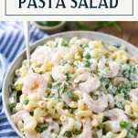 Close up side shot of a spoon in a bowl of shrimp pasta salad with text title box at top