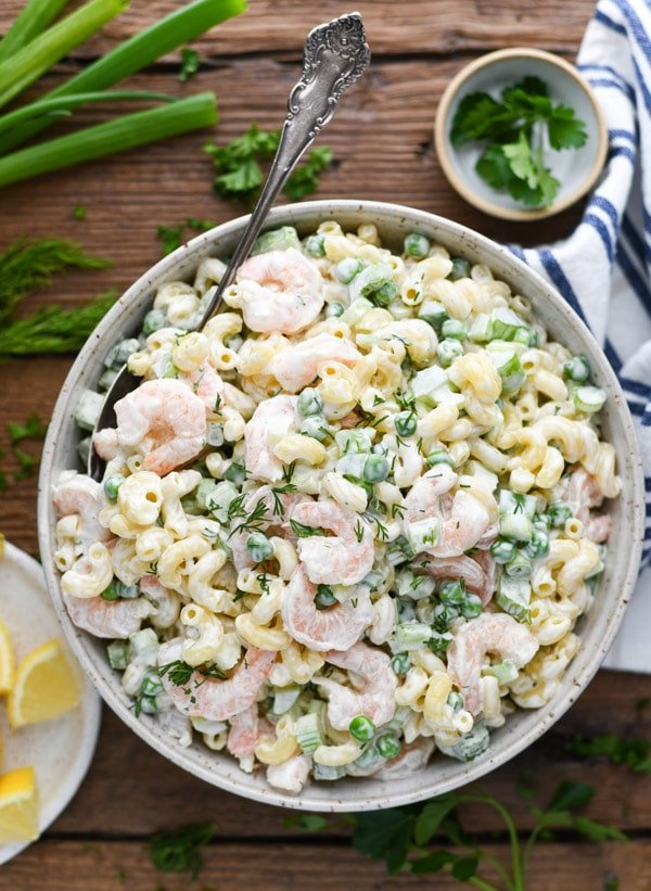 Overhead shot of a bowl of cold shrimp pasta salad on a table with blue and white striped towel