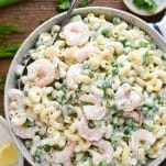 Close overhead image of a bowl of lemon shrimp pasta salad surrounded by fresh parsley and lemons on the table