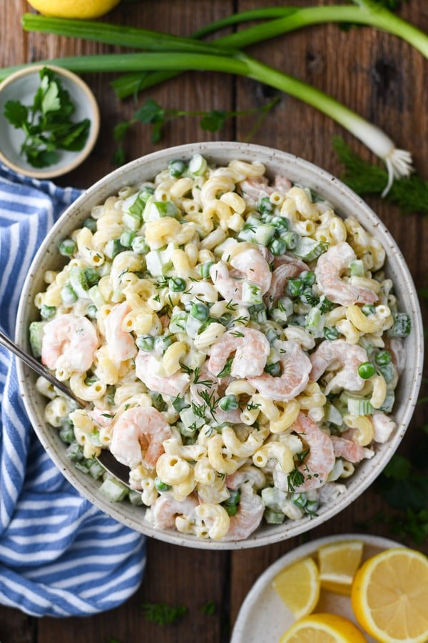 Overhead shot of a bowl of shrimp pasta salad with mayo, lemon, peas and dill on a wooden table.