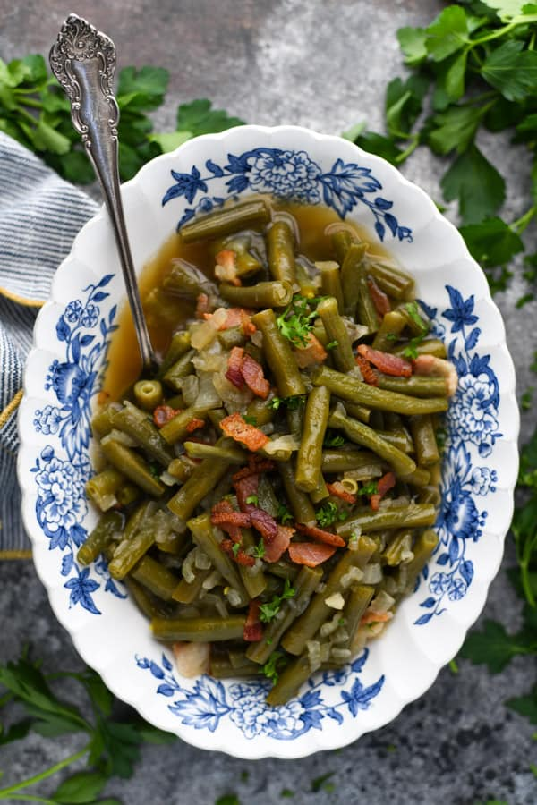 Overhead image of fresh green beans cooked country style with bacon and served in a blue and white dish