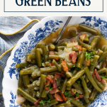 Overhead shot of southern style green beans with bacon and a text title box at top