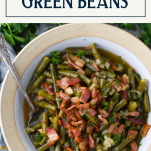 Overhead shot of a bowl of fresh green beans cooked country style with text title box at top